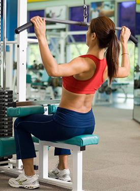 Woman in the gym pulling down weights | Mitchell Medical