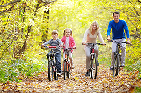 Family on a bike ride in the green forest | Mitchell Medical