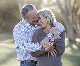 Old couple smiling and holding each other outside | Mitchell Medical